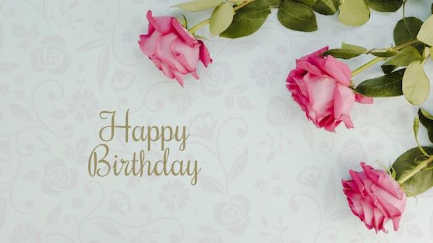 Feliz cumpleaños maqueta y flores vista superior