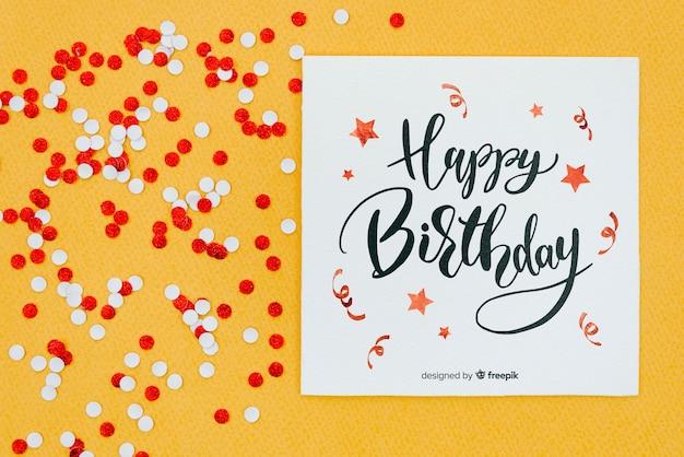 Feliz cumpleaños en tarjeta con confeti rojo y blanco