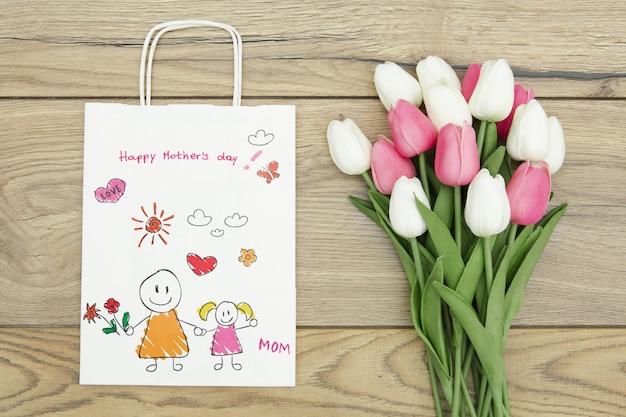 Feliz día de la madre con bolsa de regalo y tulipanes