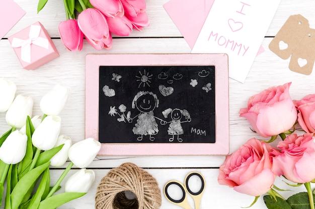 Feliz día de la madre con dibujo de pizarra y flores.