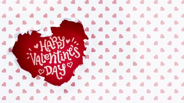 Feliz día de san valentín letras en agujero en forma de corazón