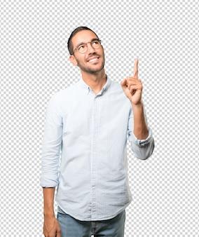 Feliz joven apuntando hacia arriba con su dedo