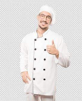Feliz joven chef gesticulando que todo está bien