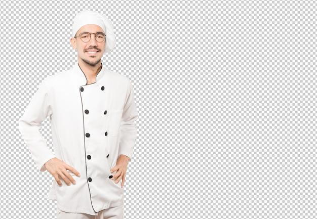 Feliz joven chef posando sobre fondo