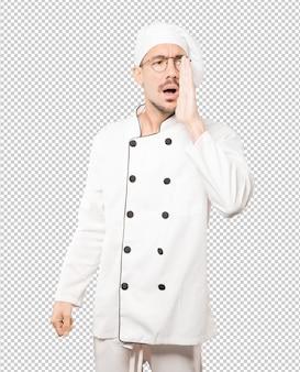 Feliz joven chef tratando de decir algo con fuerza