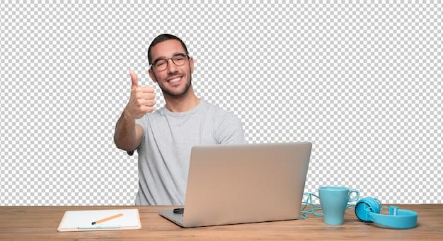 Feliz joven haciendo un gesto bien sentado en su escritorio