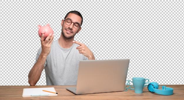 Feliz joven sentado en su escritorio y sosteniendo una alcancía