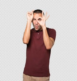Feliz joven usando sus manos como binoculares