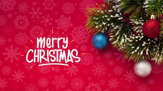 Feliz navidad y hojas de pino sobre fondo rojo de navidad