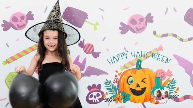 Feliz niña de halloween con globos negros