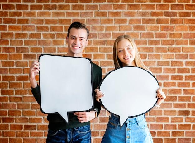 Feliz pareja joven linda sosteniendo un cartel vacío