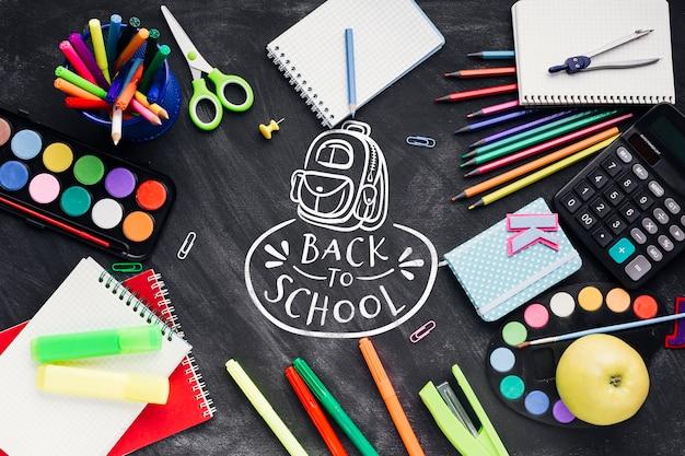 Flat recostado a la escuela con coloridos suministros