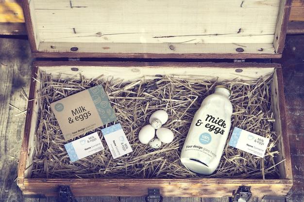 Fles melk en visitekaartjes in houten kist mockup