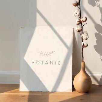 Flor de algodón en un jarrón por una tarjeta en blanco sobre un piso de madera