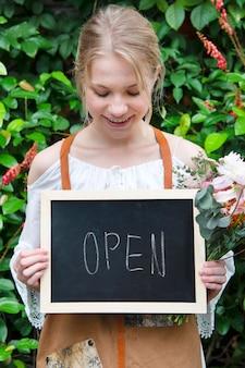 Floreria sosteniendo una maqueta de letrero de tablero abierto