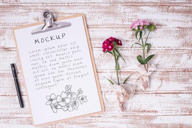 Flores de vista superior con maqueta de portapapeles