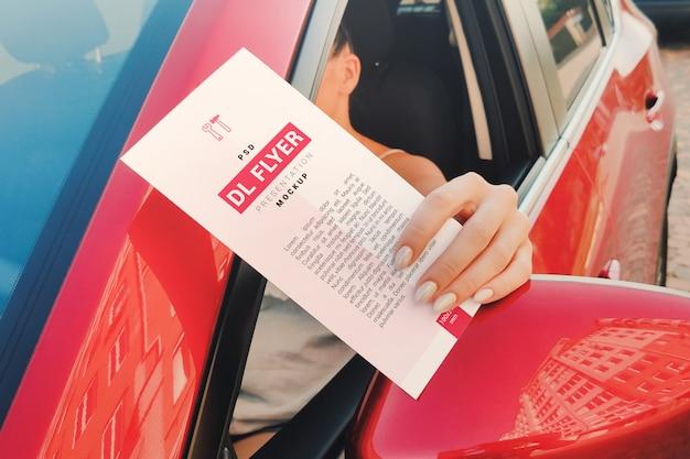 Folleto publicitario en la mano de una niña sentada en una maqueta de coche
