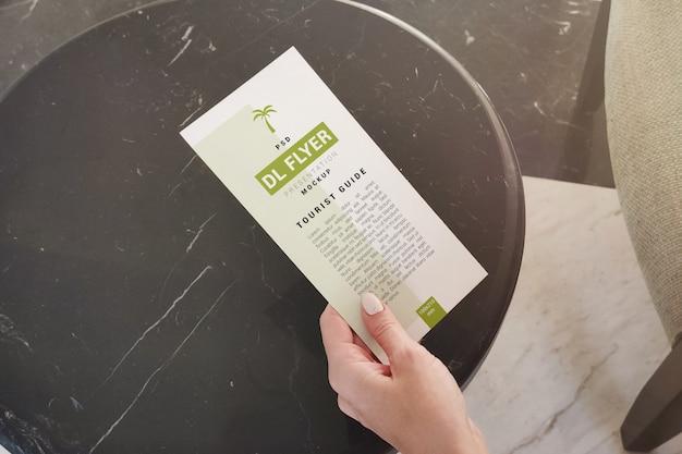 Folleto publicitario en mano sobre maqueta de mesa de café