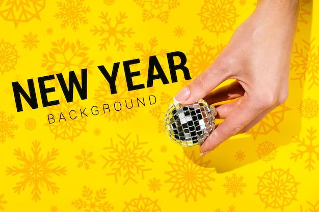 Fondo de año nuevo con mano sosteniendo una bola de navidad