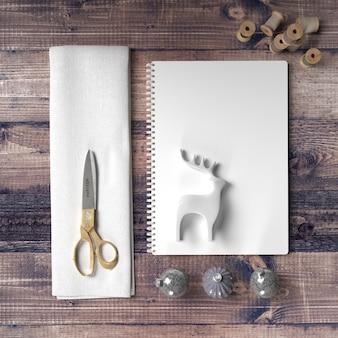 Forbici e carta per fare una decorazione di renne sul tavolo di legno