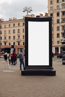 Foto di un grande cartellone che si trova sulla strada, dove camminano molte persone