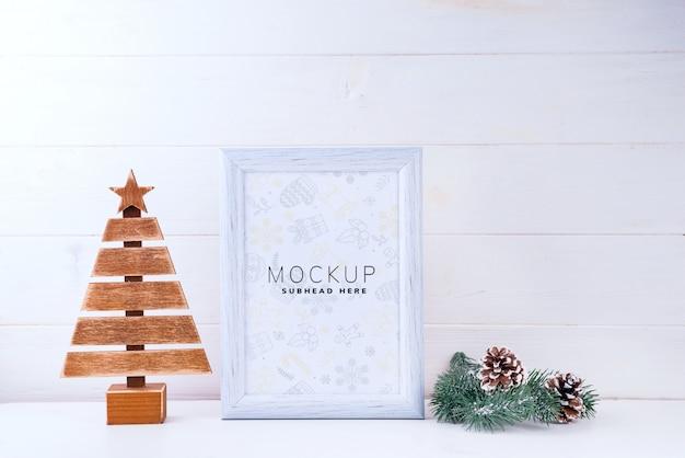 Foto maqueta con marco blanco, árbol de madera y ramas de pino sobre fondo blanco de madera