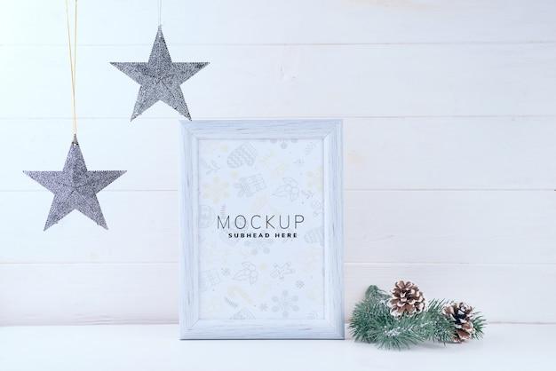 Foto maqueta con marco blanco, estrellas y ramas de pino sobre fondo blanco de madera