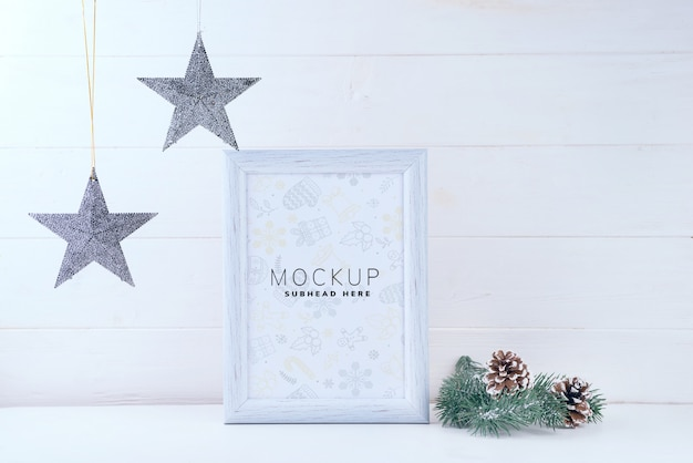Foto mock up met wit frame, sterren en pijnboomtakken op witte houten achtergrond