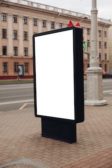 Foto van een groot reclamebord dat op straat staat, waar veel mensen lopen