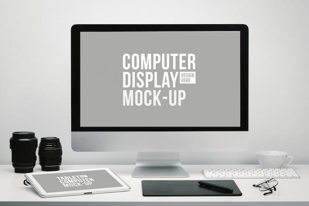 Fotograafwerkruimte met leeg computerscherm en tablet voor mockup op bureau met toetsenbord, cameralens, bril, koffiekopje en pentablet