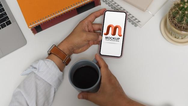 Fotografía cenital del trabajador de oficina masculino que usa un teléfono inteligente simulado mientras toma un café en el espacio de trabajo