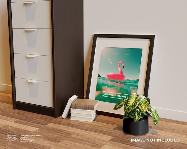 Frame poster mockup op de vloer naast de kast