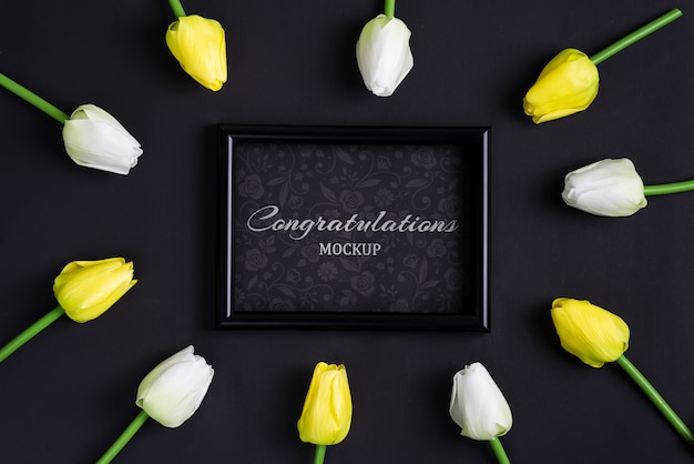 Frisse witte en gele tulpenbloemen met zwarte fotolijst
