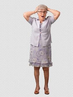 Full body donna senior frustrata e disperata, arrabbiata e triste con le mani sulla testa
