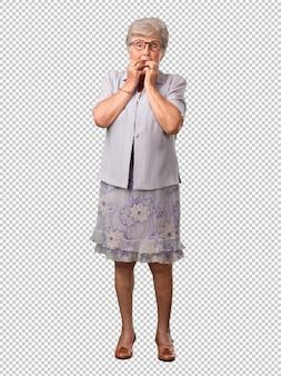 Full body senior vrouw bijt op spijkers, nerveus en erg angstig en bang voor de toekomst, voelt paniek en stress