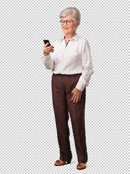 Full body senior vrouw blij en ontspannen, het aanraken van de mobiel, met behulp van het internet en sociale netwerken, positief gevoel van de toekomst en moderniteit