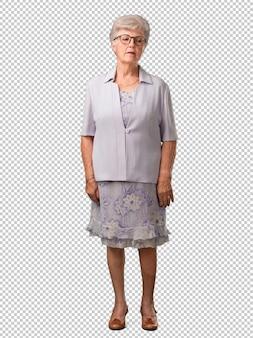 Full body senior vrouw twijfelt en verward, denkend aan een idee of bezorgd over iets