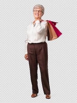 Full body senior vrouw vrolijk en lachend, erg enthousiast met een boodschappentas, klaar om te gaan winkelen en op zoek naar nieuwe aanbiedingen