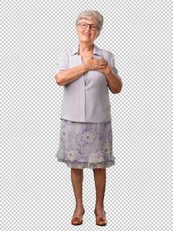 Full body senior woman facendo un gesto romantico, innamorato di qualcuno o mostrando affetto per qualche amico