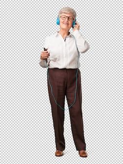Full body senior woman felice e divertente, ascoltando musica, cuffie moderne, felice sentendo il suono e il ritmo