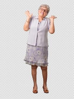 Full body senior woman pazza e disperata, urlando incontrollabile, divertente pazzo che esprime libertà e selvaggio