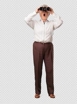 Full body senior woman sorpreso e stupito, guardando con il binocolo in lontananza qualcosa di interessante, concetto di opportunità future