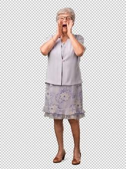 Full body senior woman urlando felice, sorpreso da un'offerta o una promozione, a bocca aperta, saltando e orgoglioso