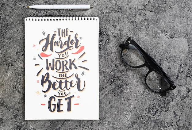 Gafas al lado del cuaderno con mensaje inspirador