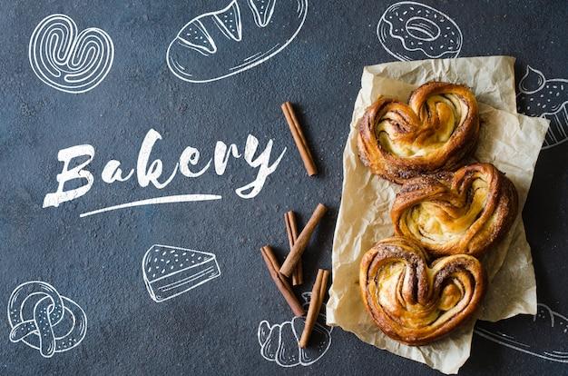 Gebakken vers geurende kaneelbroodjes. traditionele huisgemaakte gebakjes op donkere achtergrond.