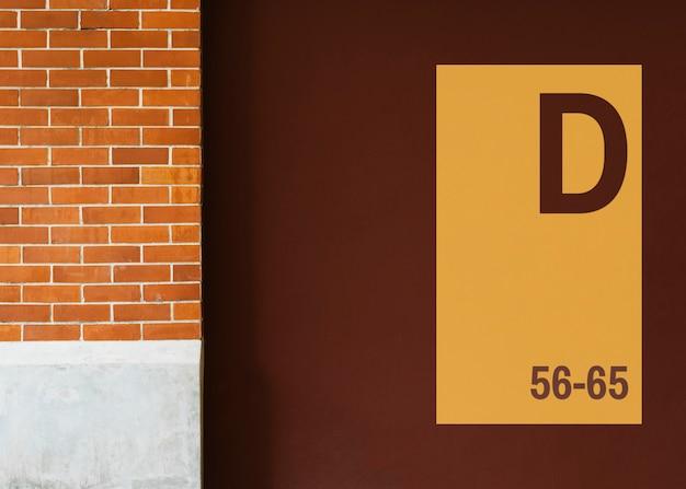 Geel uithangbordmodel op een bruine muur