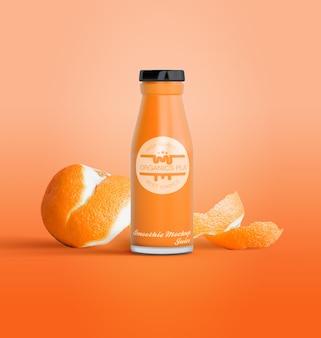 Geïsoleerde fles vruchtensap en sinaasappelen