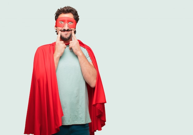 Gekke man als een superheld dwingt een glimlach op zijn gezicht met beide wijsvingers