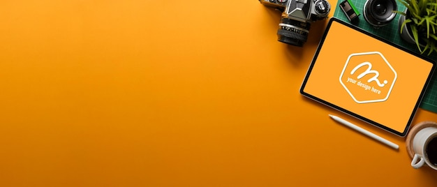Gele creatieve plat lag werkruimte met digitale tablet