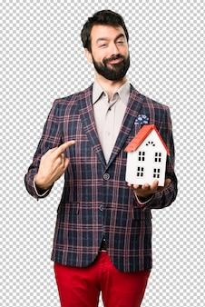 Gelukkig goed geklede man met een klein huis